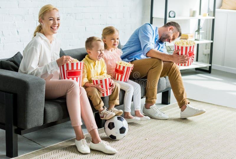 família feliz que come a pipoca ao sentar-se junto no sofá imagens de stock
