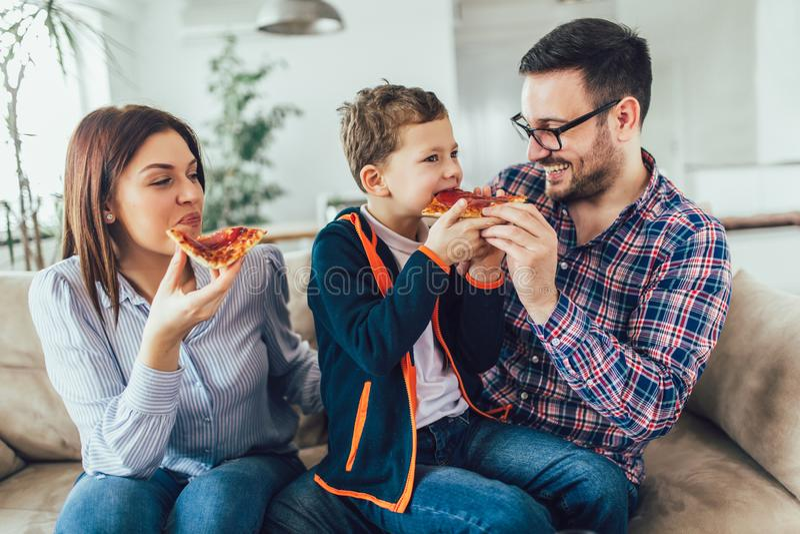 Família feliz que come a pizza ao sentar-se no sofá em casa imagens de stock royalty free