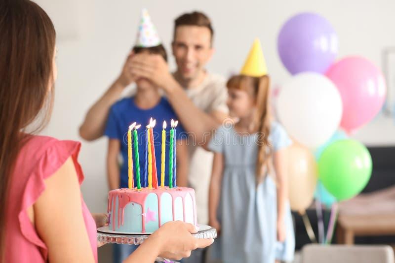Família feliz que comemora o aniversário com bolo em casa foto de stock
