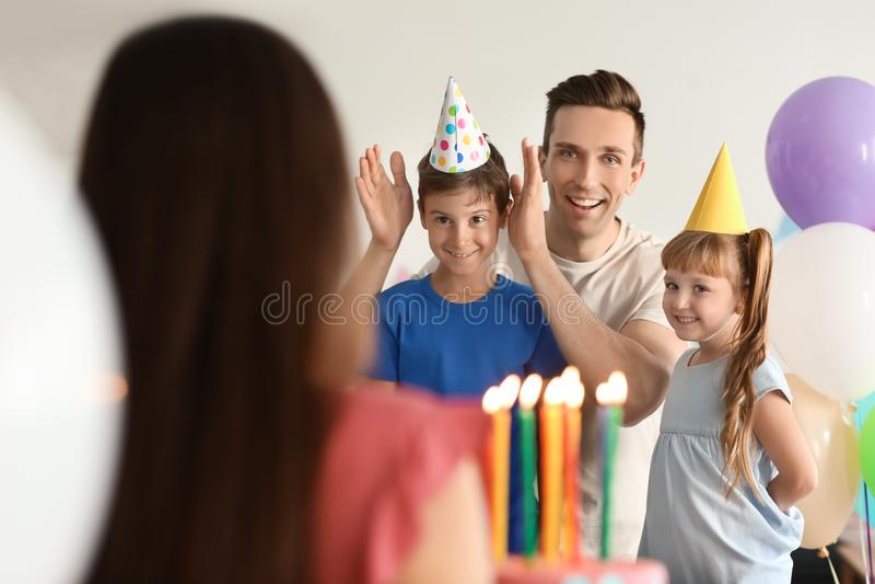 Família feliz que comemora o aniversário com bolo em casa imagem de stock royalty free