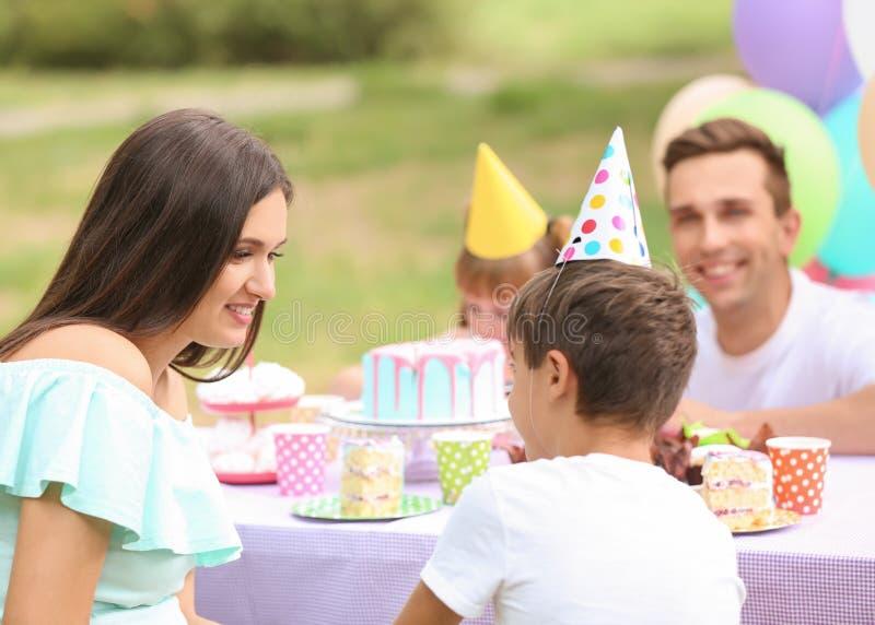 Família feliz que comemora o aniversário na tabela fora fotos de stock royalty free