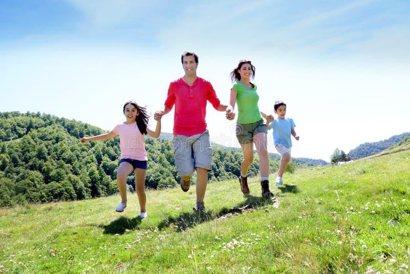 Família feliz que corre alegremente na paisagem bonita fotografia de stock