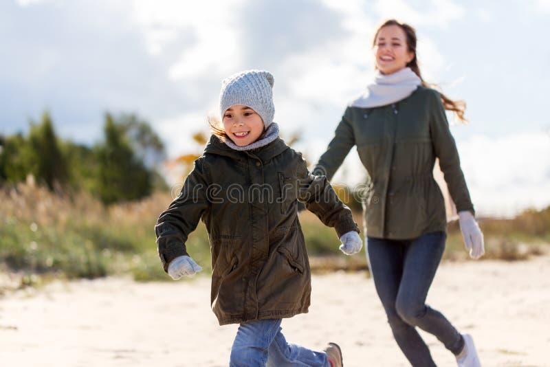 Família feliz que corre ao longo da praia do outono imagens de stock
