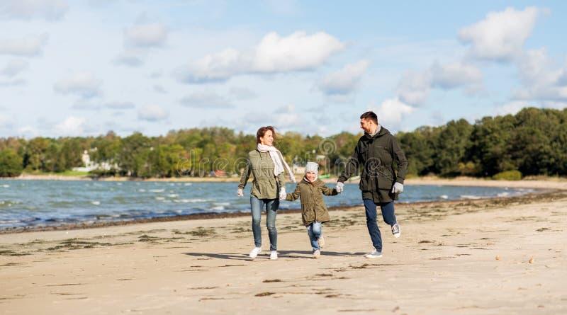 Família feliz que corre ao longo da praia do outono fotografia de stock royalty free