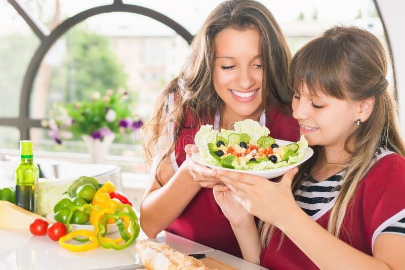 Família feliz que cozinha a salada Refeição do vegetariano na cozinha foto de stock royalty free