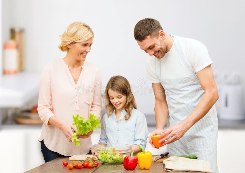 Família feliz que cozinha a salada vegetal para o jantar foto de stock royalty free