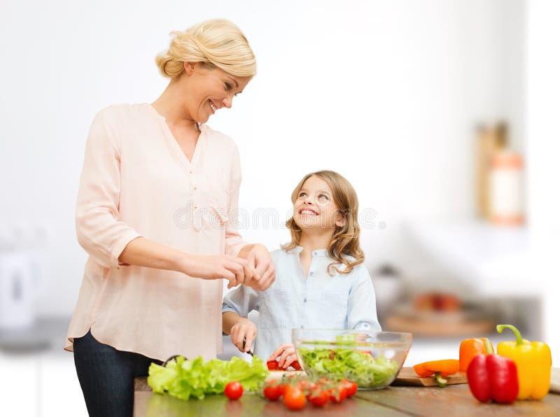 Família feliz que cozinha a salada vegetal para o jantar imagem de stock royalty free