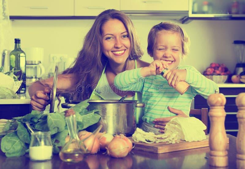 Família feliz que cozinha a sopa imagens de stock royalty free