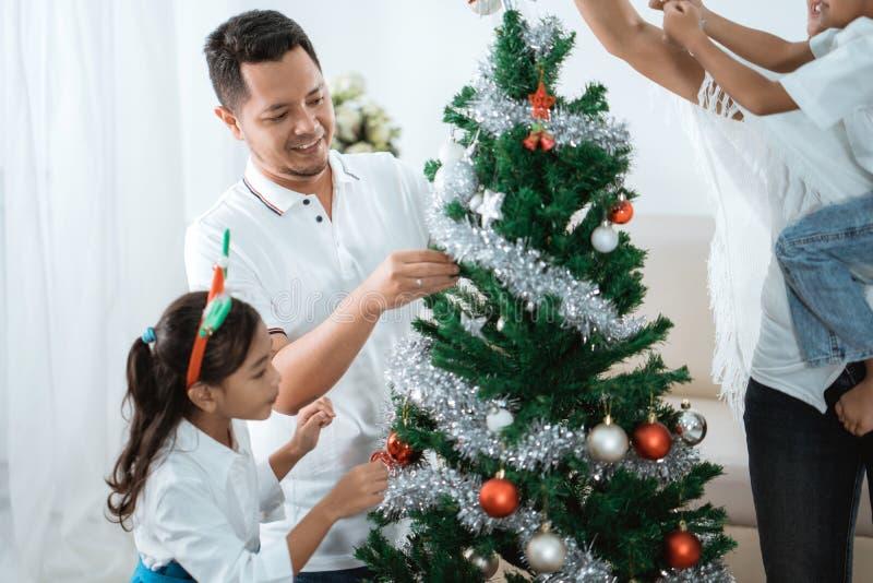 Família feliz que decora a árvore de Natal fotografia de stock