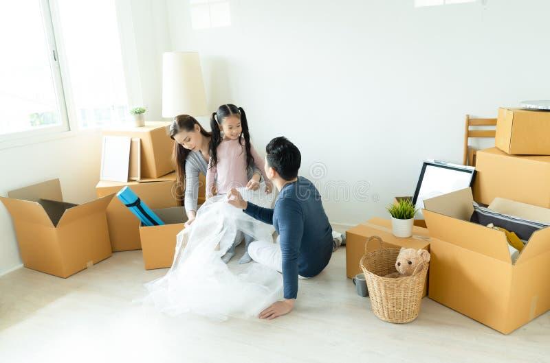 Família feliz que desembala caixas de cartão na casa nova Conce móvel imagens de stock royalty free