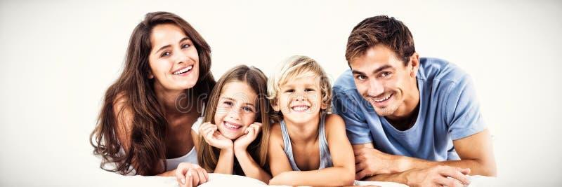 Família feliz que encontra-se em uma cama foto de stock
