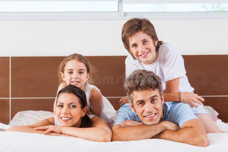 Família feliz que encontra-se em uma cama imagens de stock