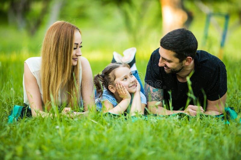 Família feliz que encontra-se na grama no parque do verão Olhar novo da filha no pai fotos de stock