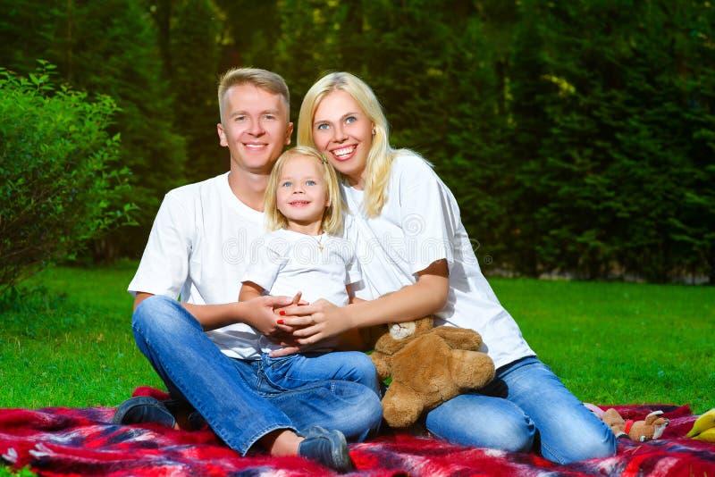 Família feliz que encontra-se na grama no verão Piquenique fotografia de stock royalty free