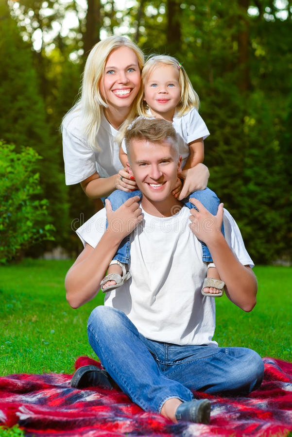 Família feliz que encontra-se na grama no verão Piquenique fotografia de stock