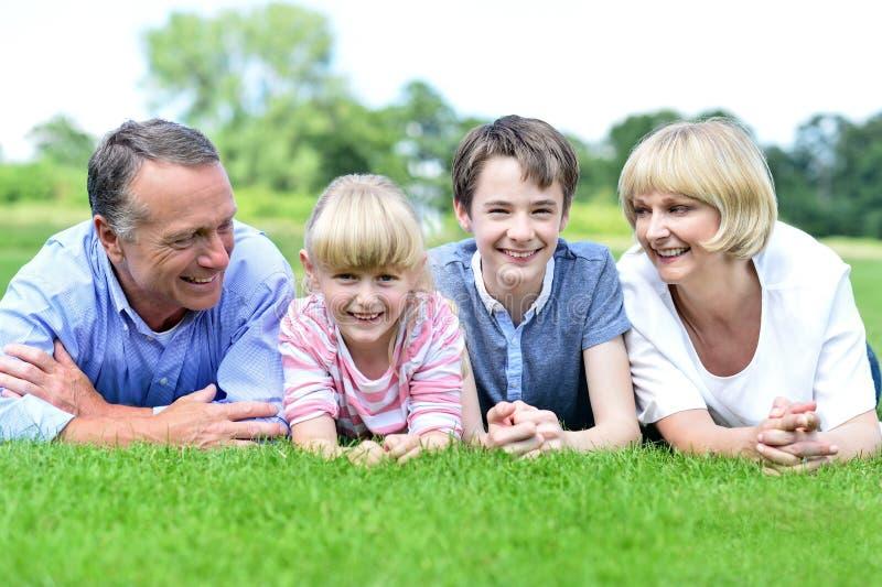Família feliz que encontra-se na pastagem verde luxúria imagens de stock royalty free
