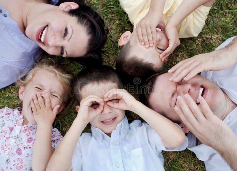 Família feliz que encontra-se na terra fotos de stock royalty free