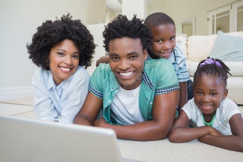 Família feliz que encontra-se no assoalho usando o portátil foto de stock royalty free