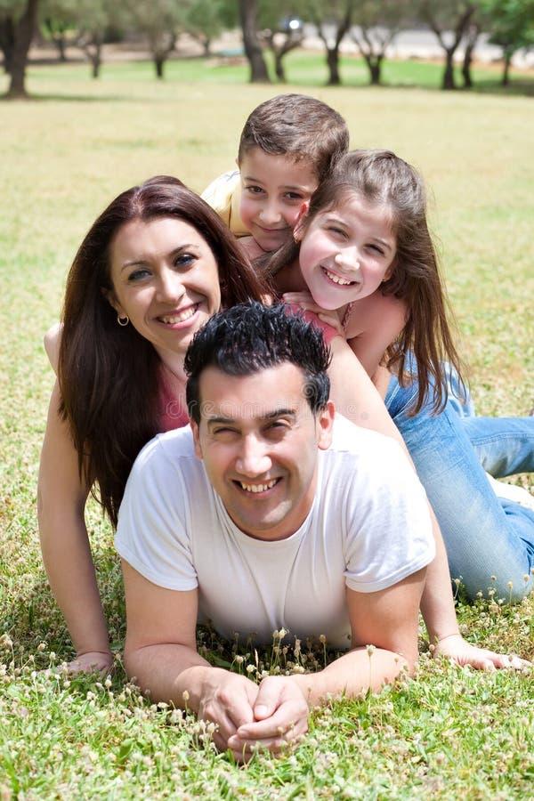 Família feliz que encontra-se no campo de grama fotografia de stock