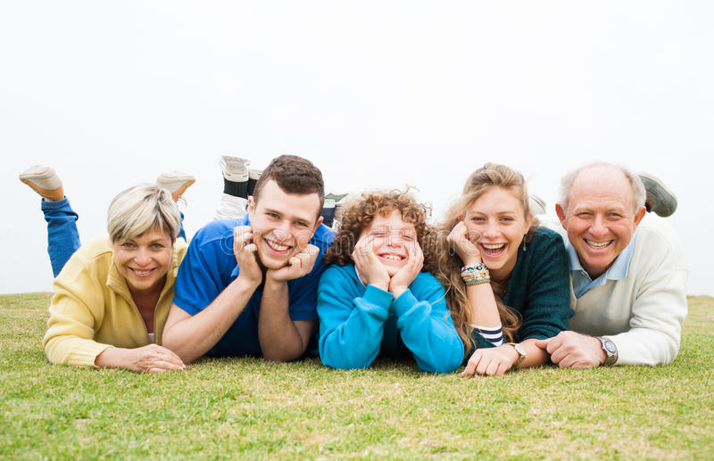 Família feliz que encontra-se no gramado verde foto de stock royalty free