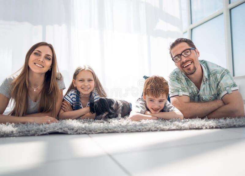 Família feliz que encontra-se no tapete na sala na casa nova imagens de stock