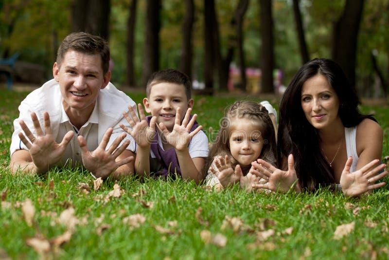 Família feliz que encontra-se para baixo no jardim imagens de stock
