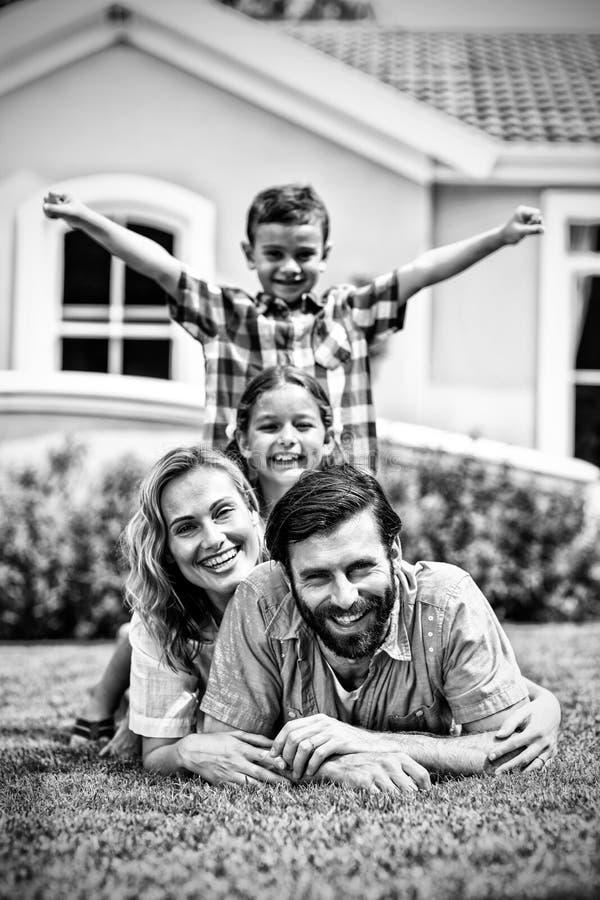 Família feliz que encontra-se sobre se na jarda imagens de stock