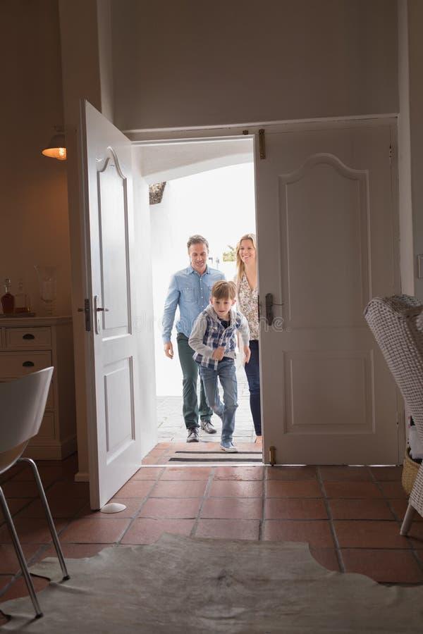 Família feliz que entra na casa fotografia de stock royalty free
