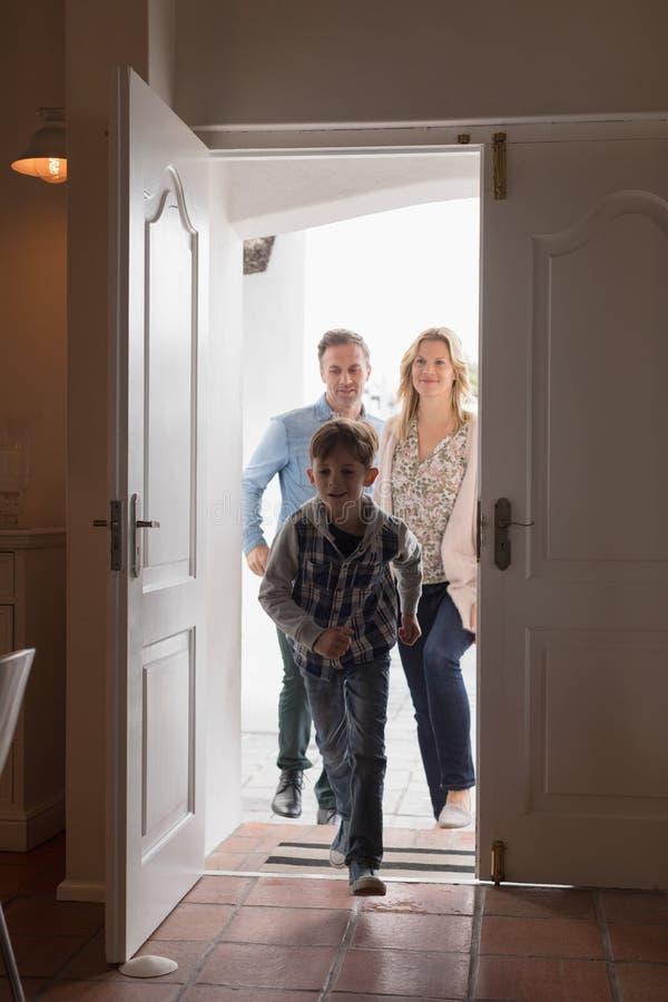 Família feliz que entra na casa imagens de stock