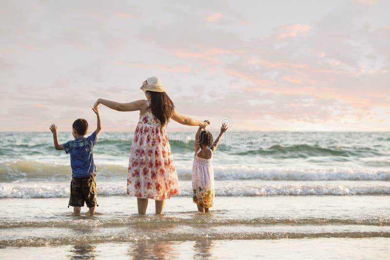 Família feliz que está na praia fotografia de stock