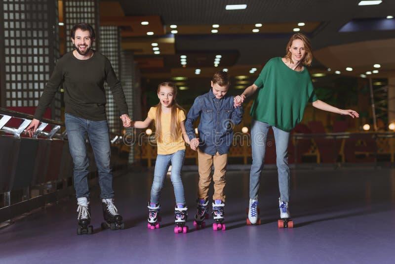 família feliz que guarda as mãos ao patinar junto imagens de stock
