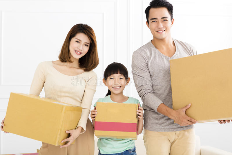 Família feliz que guarda a caixa que move-se para a casa nova fotografia de stock