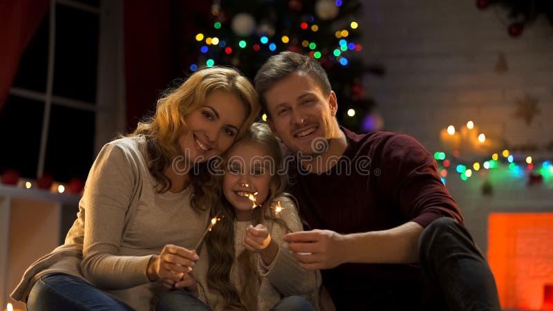 Família feliz que guarda a luz de Bengal que senta-se sob a árvore de Natal, véspera de ano novo foto de stock