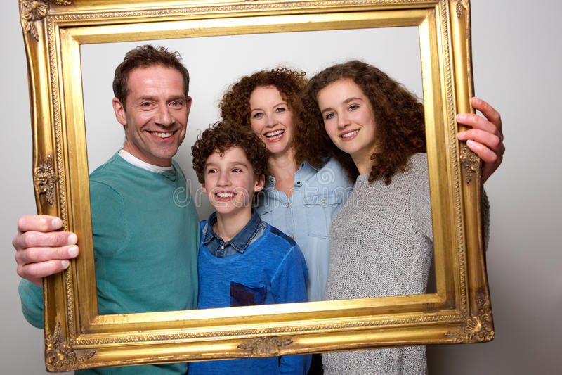Família feliz que guarda a moldura para retrato e o sorriso imagens de stock
