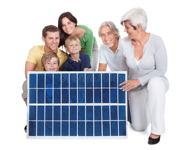 Família feliz que guarda o painel solar imagens de stock royalty free