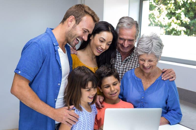 Família feliz que interage usando o portátil imagens de stock royalty free