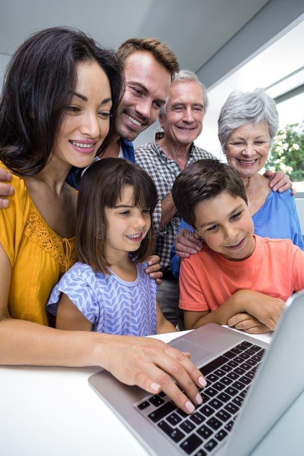 Família feliz que interage usando o portátil fotografia de stock