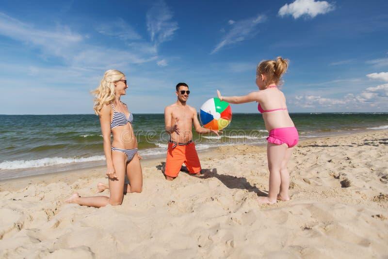 Família feliz que joga com a bola inflável na praia imagens de stock royalty free