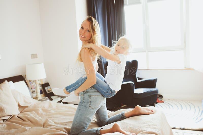Família feliz que joga em casa Filha da mãe e da criança que relaxa e que tem o divertimento na cama imagem de stock royalty free