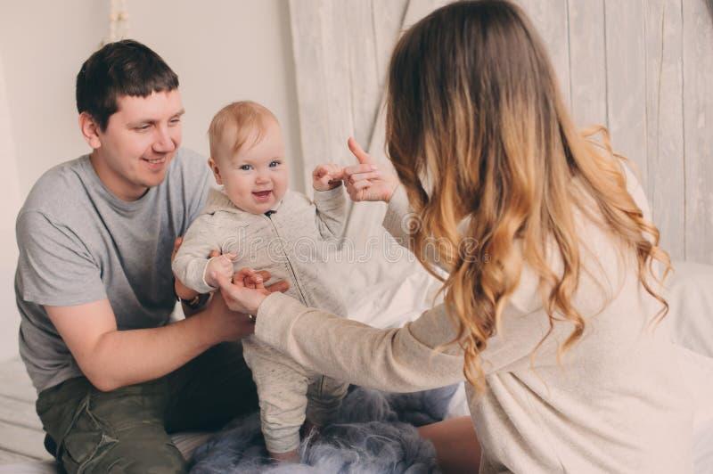 Família feliz que joga em casa na cama Captação do estilo de vida da mãe, do pai e do bebê imagem de stock royalty free