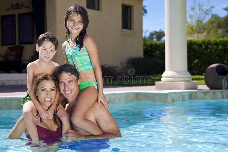 Família feliz que joga em uma piscina