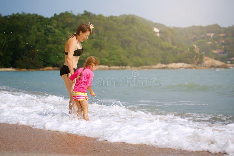 Família feliz que joga na água azul em um recurso tropical no s fotografia de stock