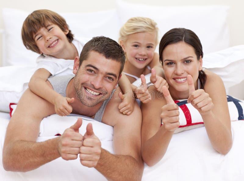 Família feliz que joga na cama do pai imagens de stock royalty free