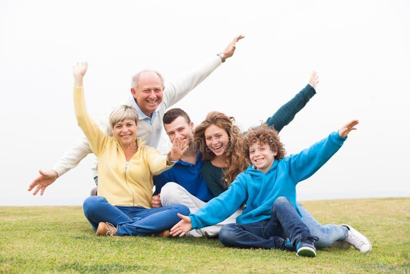 Família feliz que joga na grama foto de stock