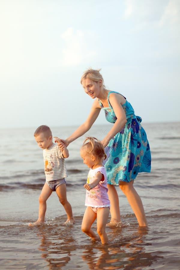 Família feliz que joga na praia fotos de stock royalty free