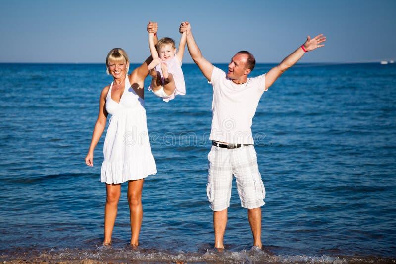 Família feliz que joga na praia imagens de stock royalty free