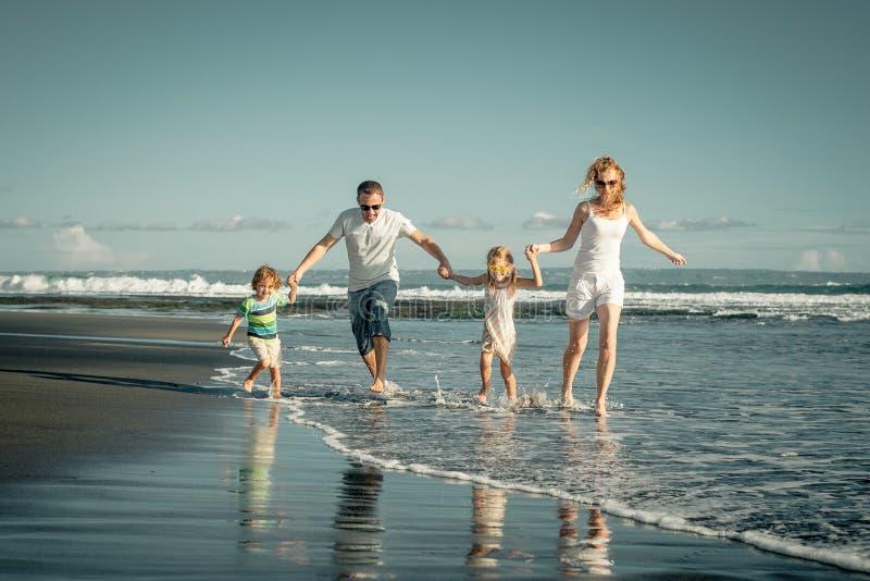 Família feliz que joga na praia no tempo do dia foto de stock royalty free