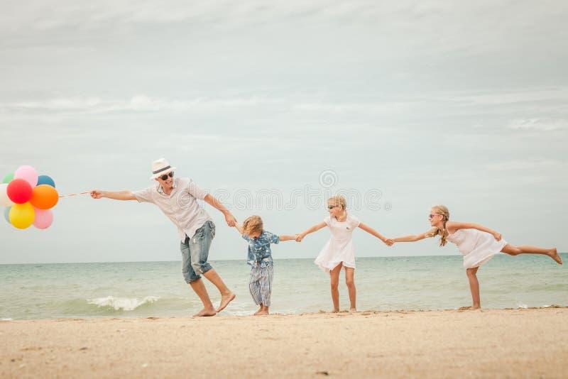 Família feliz que joga na praia no tempo do dia fotos de stock royalty free