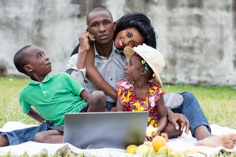Família feliz que joga no parque fotografia de stock