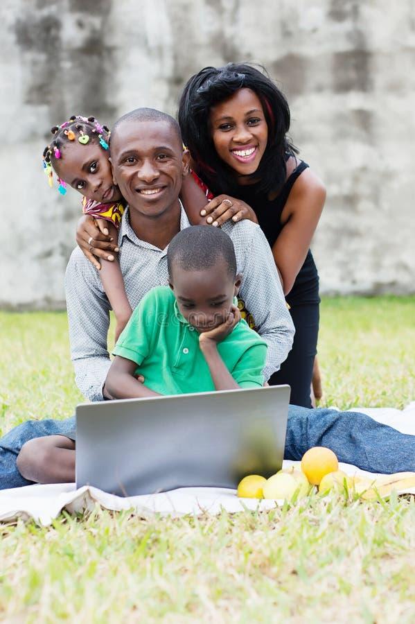 Família feliz que joga no parque imagens de stock royalty free